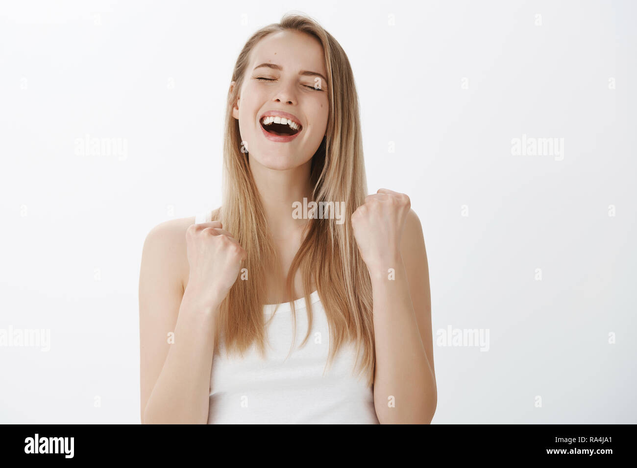 Sweet taste of success. Happy delighted and relived young woman screaming yes from victory and pleasure receiving award clenching raised fists in victory and triumoh closing eyes from satisfaction Stock Photo
