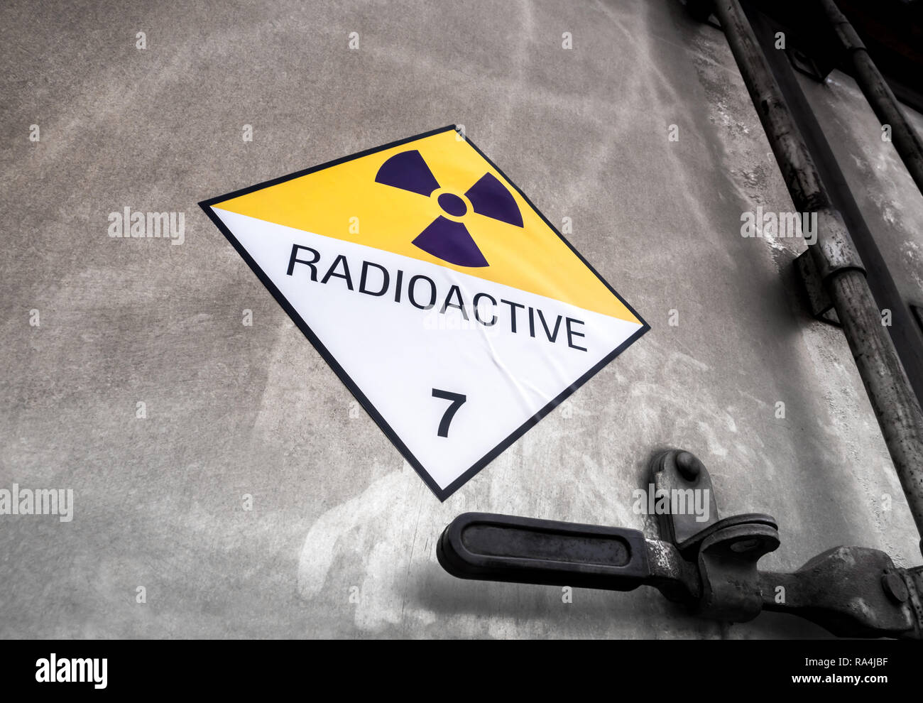Radiation warning sign on the Hazardous materials transport label Class 7 at the aluminum container of transport truck - Stock Image