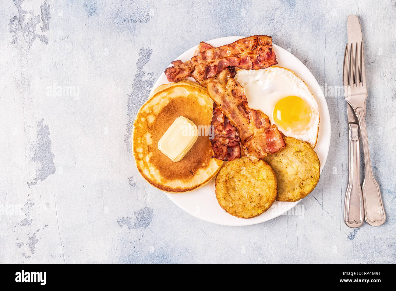 Healthy Full American Breakfast with Eggs Bacon Pancakes and Latkes, top view. - Stock Image