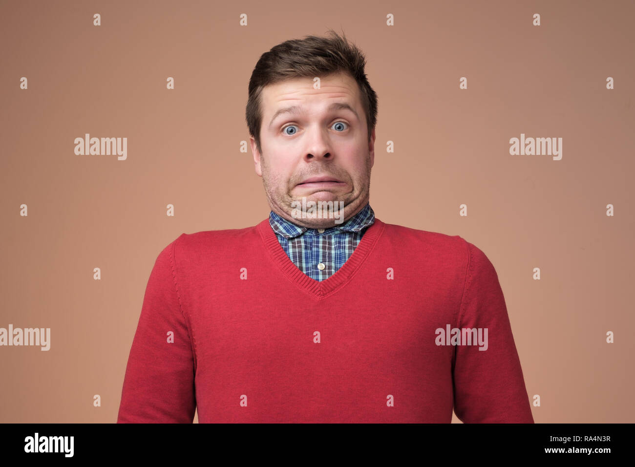 Oops. Funny caucasian man in red sweater grimacing guilty face at studio background - Stock Image