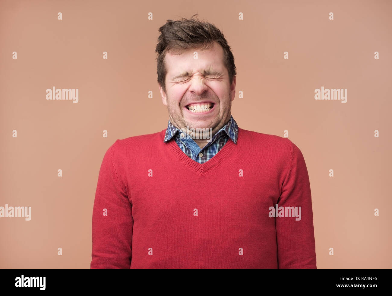 Guy grins at camera, shows white teeth, closes eyeswaiting for gift - Stock Image