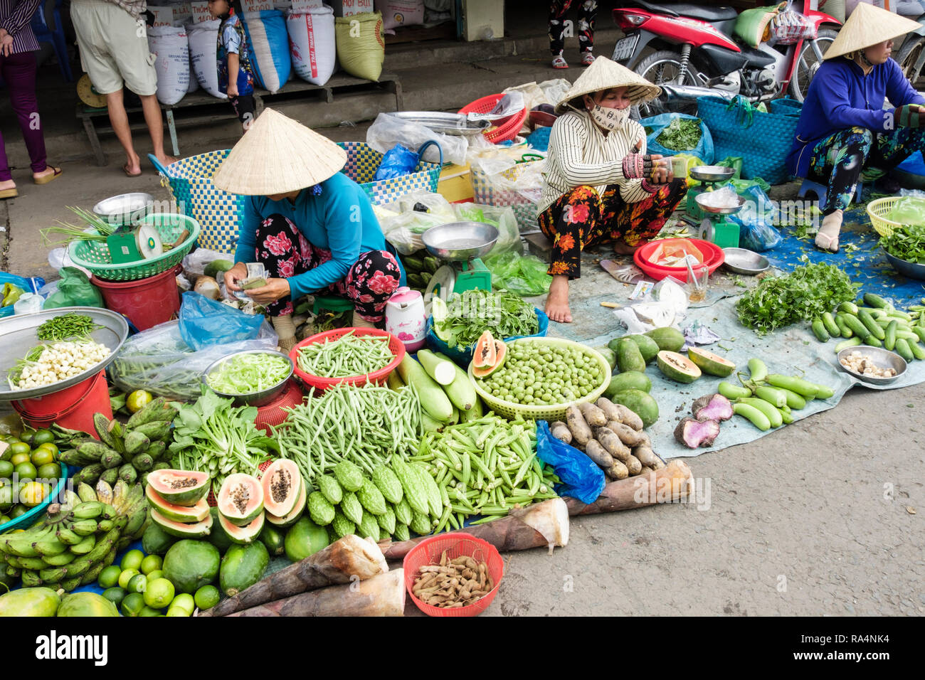 1d35101fcfa Vietnamese women stallholders wearing conical hats displaying fresh local  fruit and vegetables for sale in a