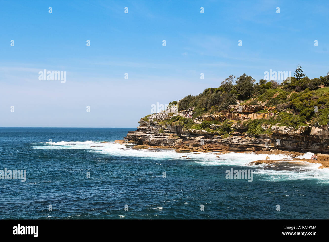 Cliffs at the coastal walk from Bondi beach to Coogee beach in Sydney on a perfect blue day in summer (Sydney, New South Wales, Australia) - Stock Image