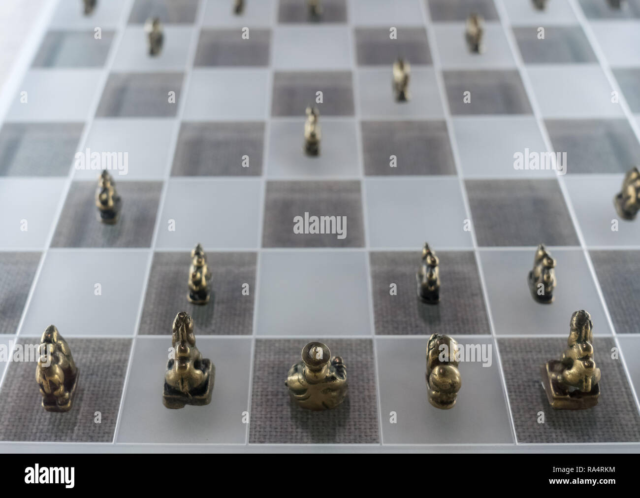 Cast metal chess men on glass board - Stock Image