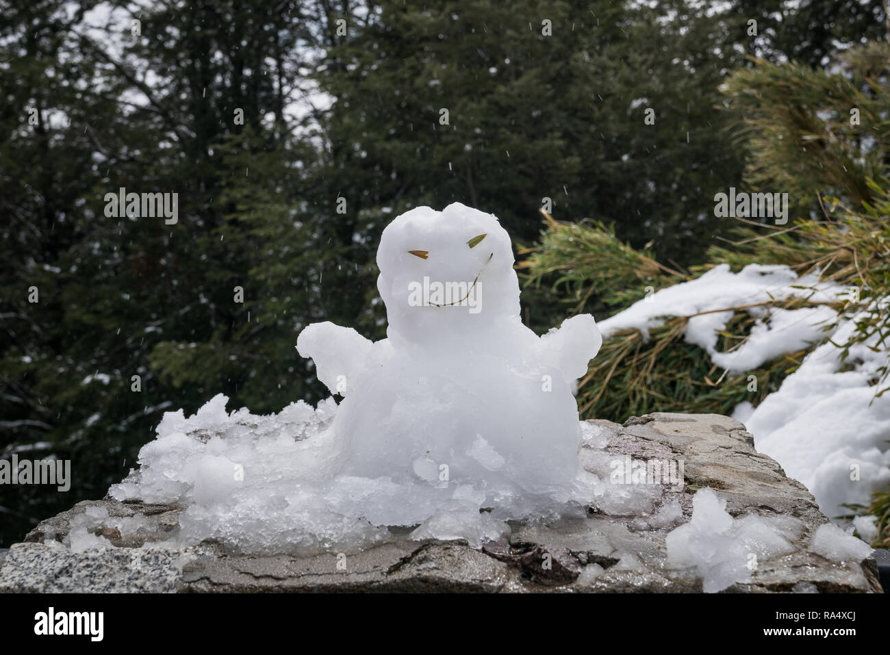 Snowman made of fresh white snow on a rock in mountain woodland conceptual of Christmas holiday season Stock Photo