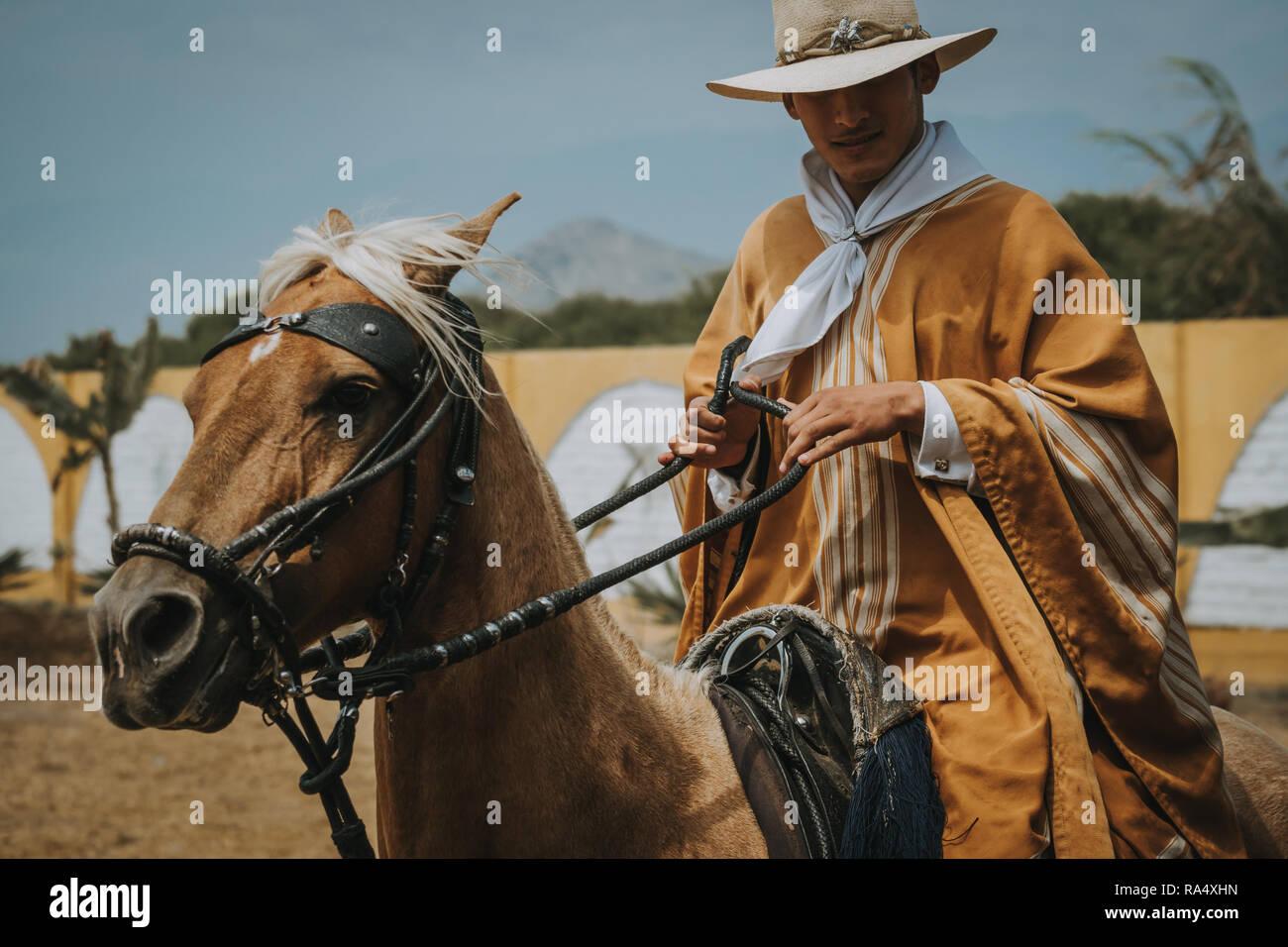 TRUJILLO, PERU - SEPTEMBER 2018 : Man in traditional clothes riding on a horse in a close up portrait, Trujillo, Peru Stock Photo