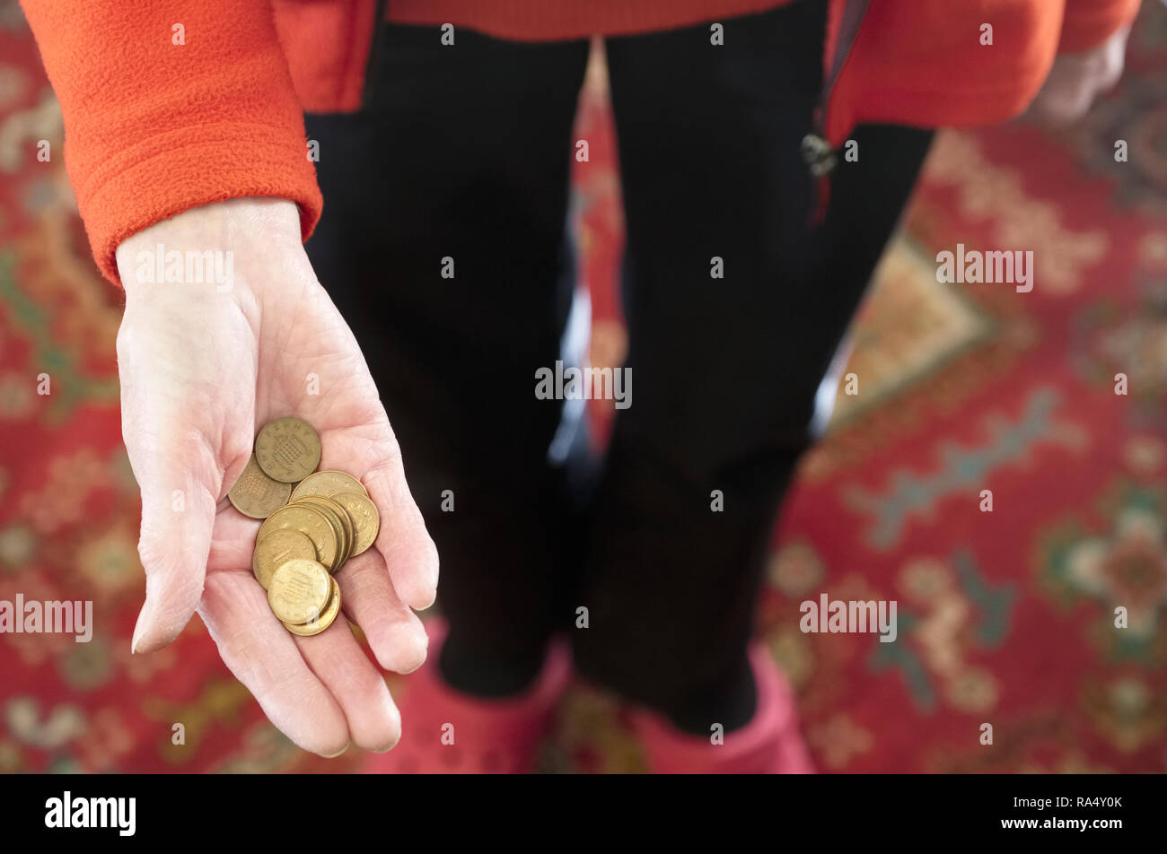 Elderly hand holding money cash loose change coins pence copper pension savings - Stock Image