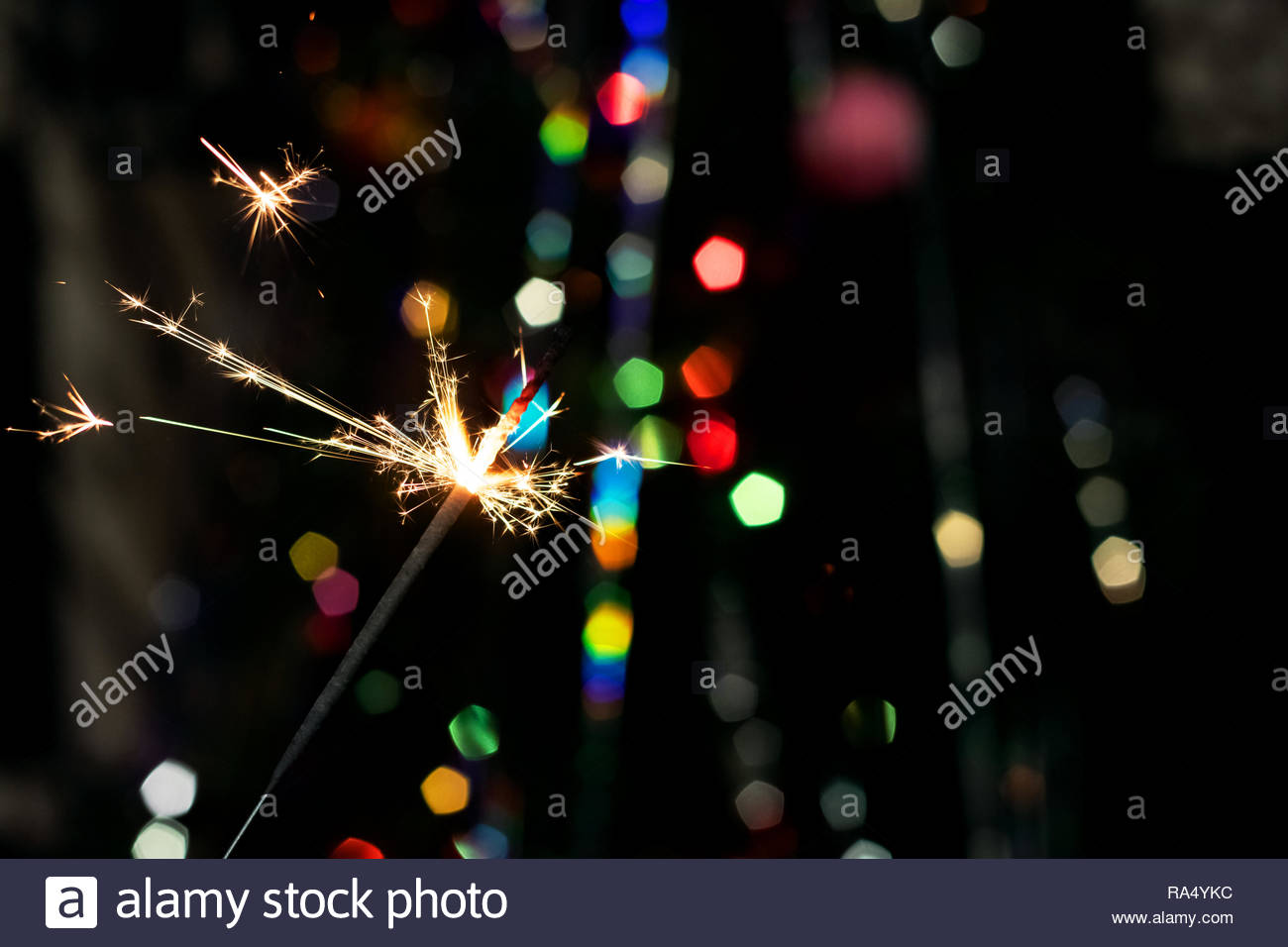 Burning sparkler on the background of New Year's fir, copy space