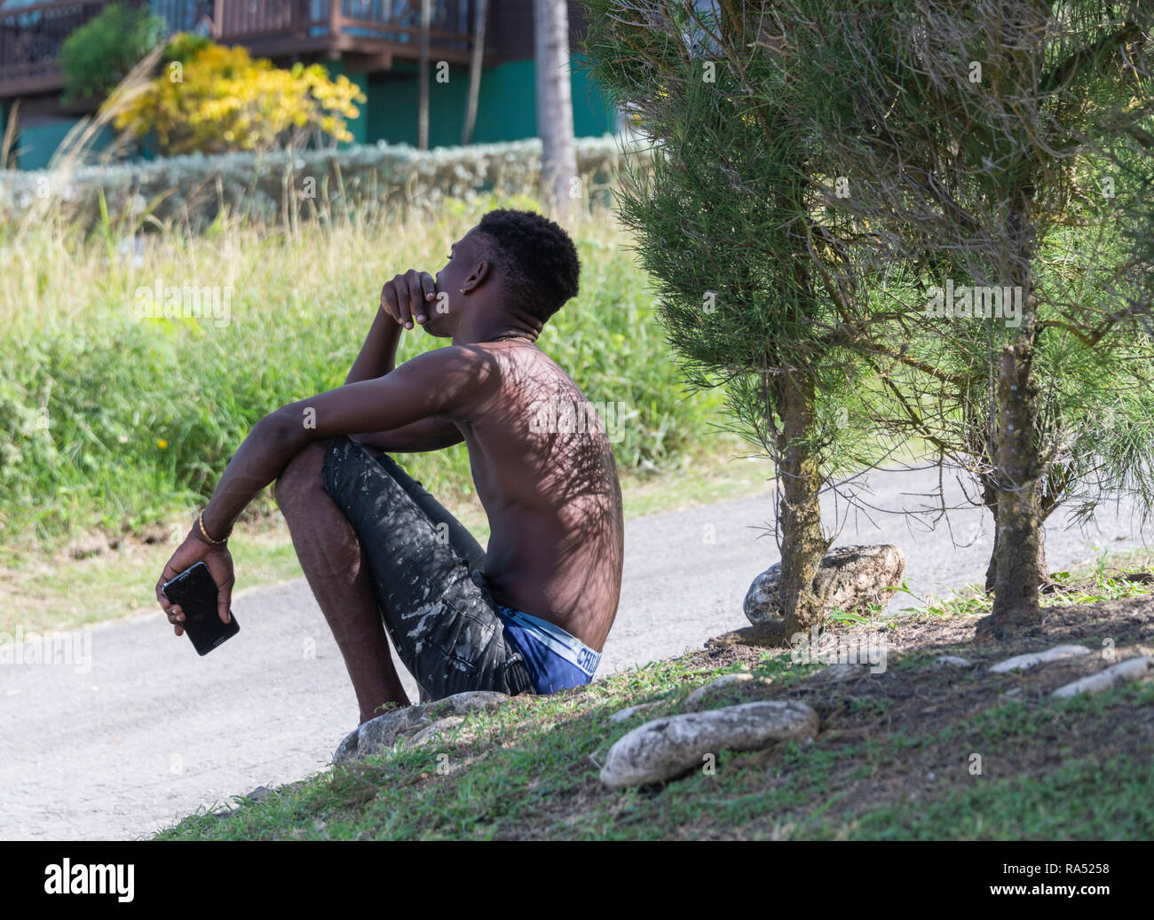 Young Barbadian male sitting at the roadside, Barbados - Stock Image