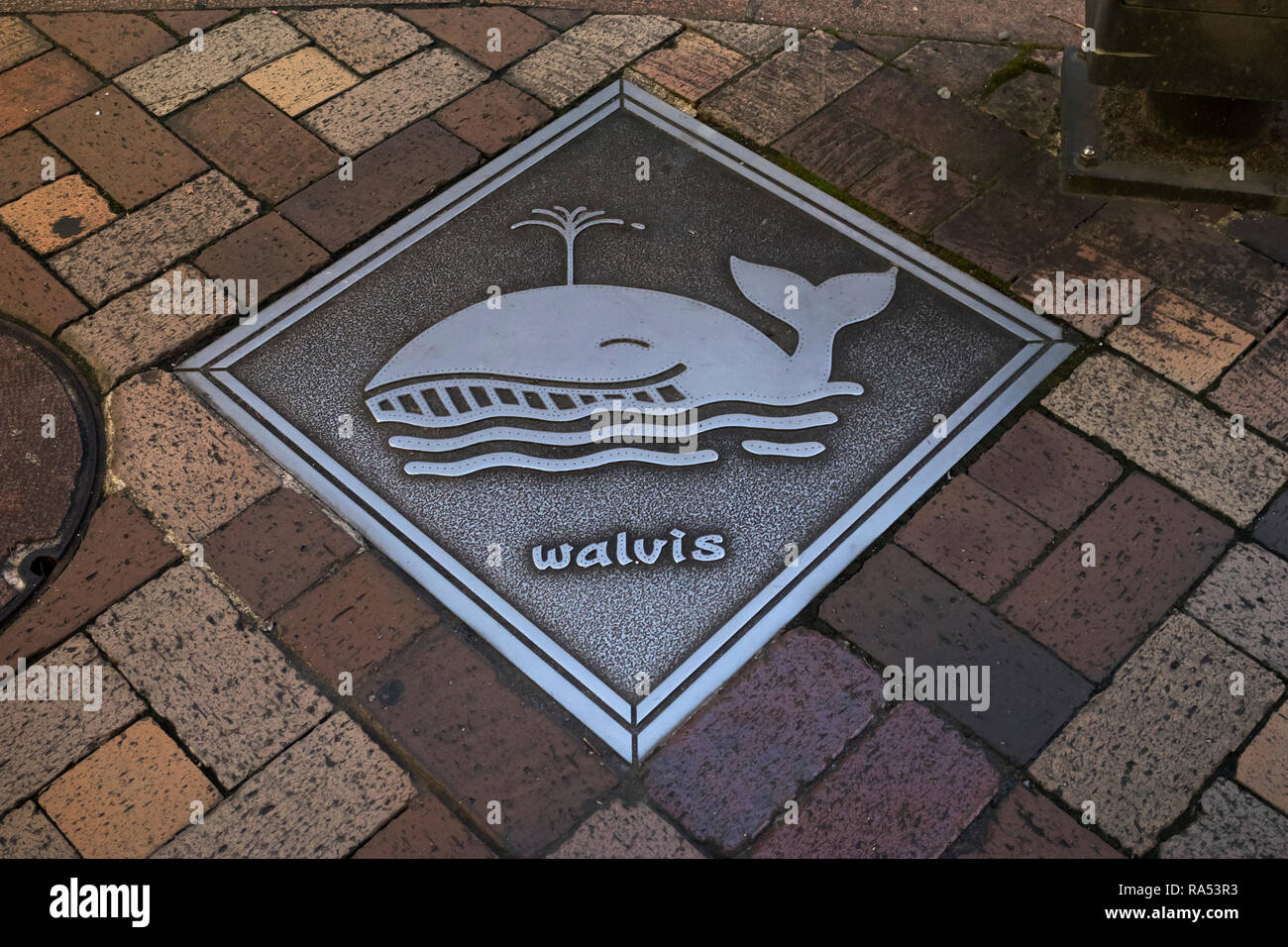 Nagasaki, Japan - October 24, 2018: Manhole cover art in Nagasaki with a whale and the dutch word Walvis - Stock Image