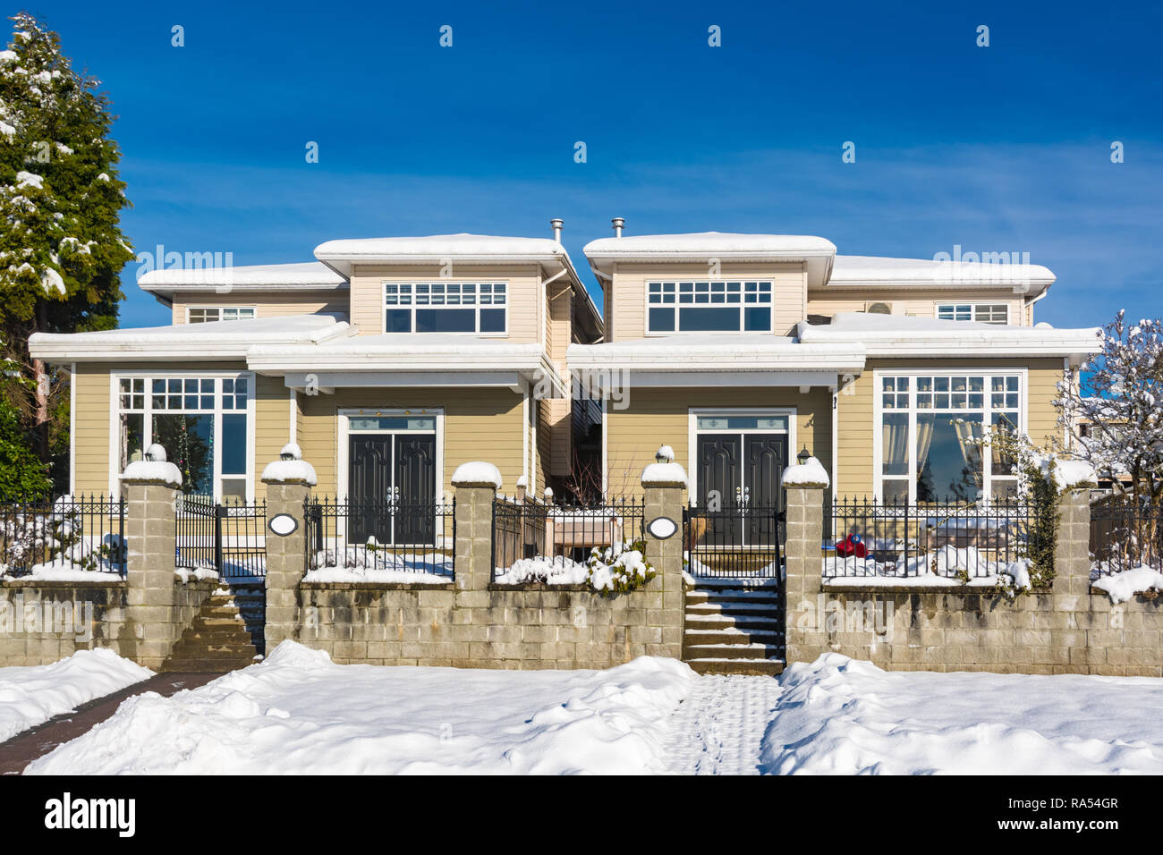 Residential duplex house with front yard in snow on winter sunny day in Canada - Stock Image
