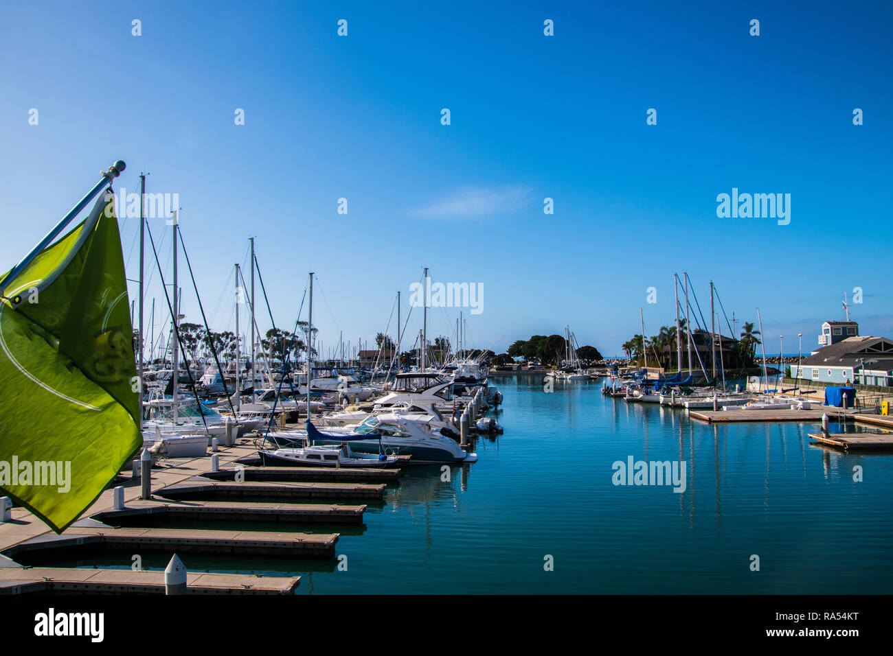Small marina with beep blue water and many sail and power boats docked in slips - Stock Image