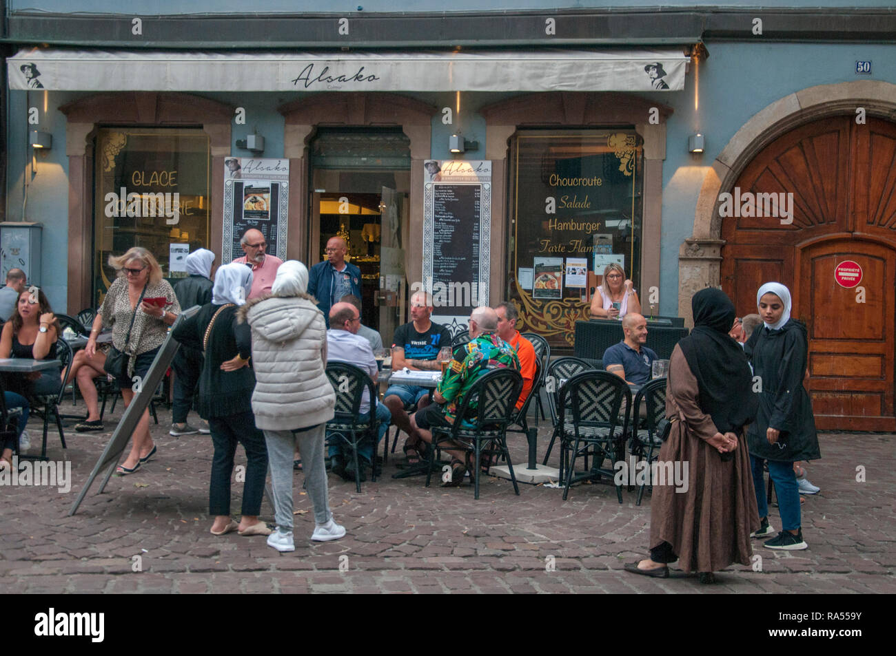Clash of cultures: female Muslim tourists observe western tourists drinking outside a bar in Colmar, Alsace, France - Stock Image