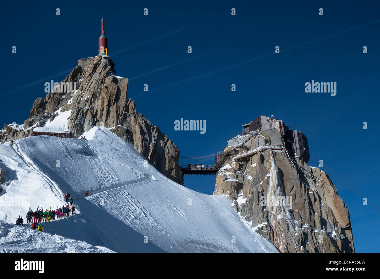 Chamonix, France - 30 Mars 2017: Line of offpiste skiers and ski tourers waiting to make their way down famous ridge (arete) on Aiguille du Midi to sk - Stock Image