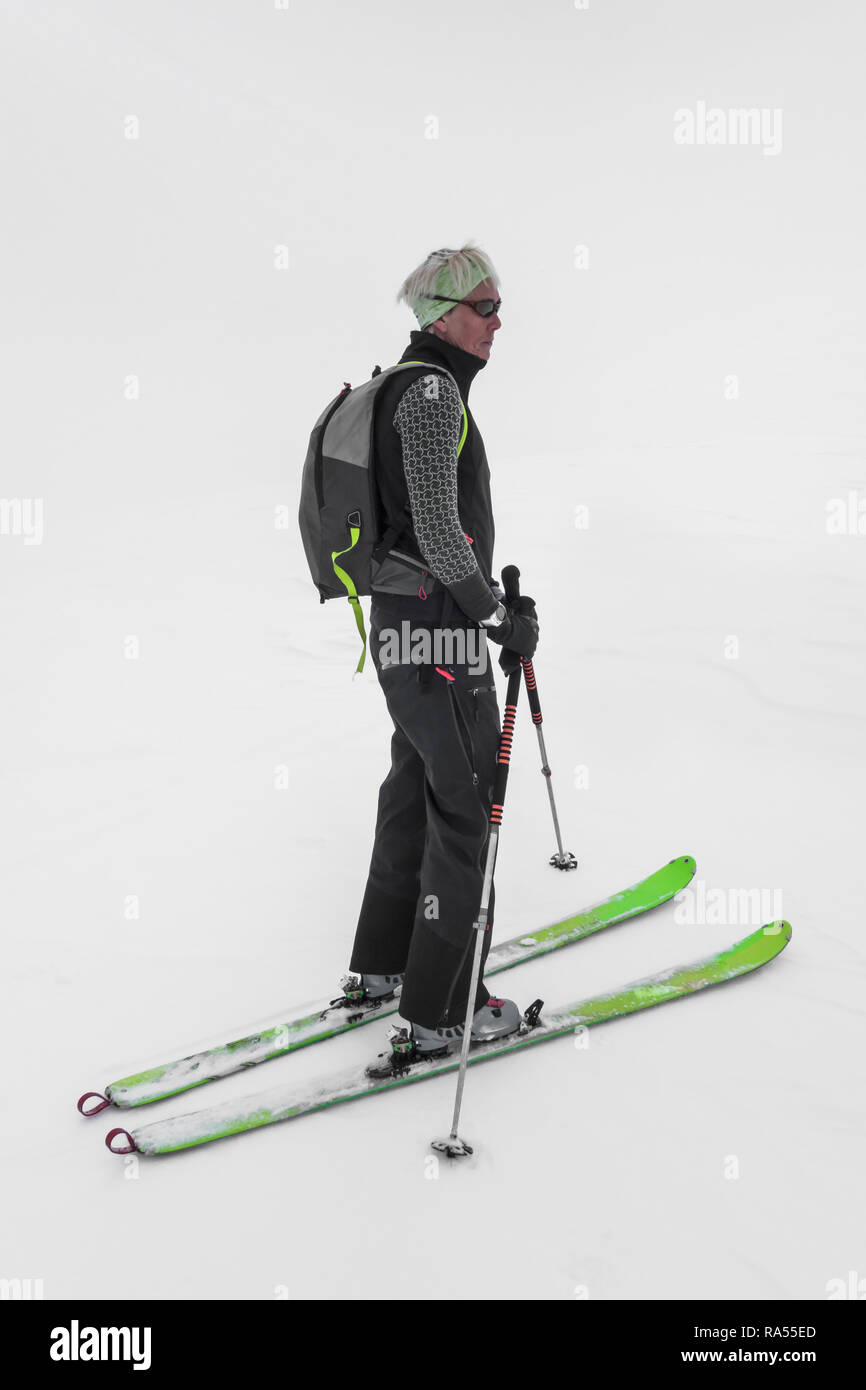 Le Tour, France - 26 March, 2018: Single blond woman on touring skis in activity winter clothing standing isolated against high key lighting white bac - Stock Image