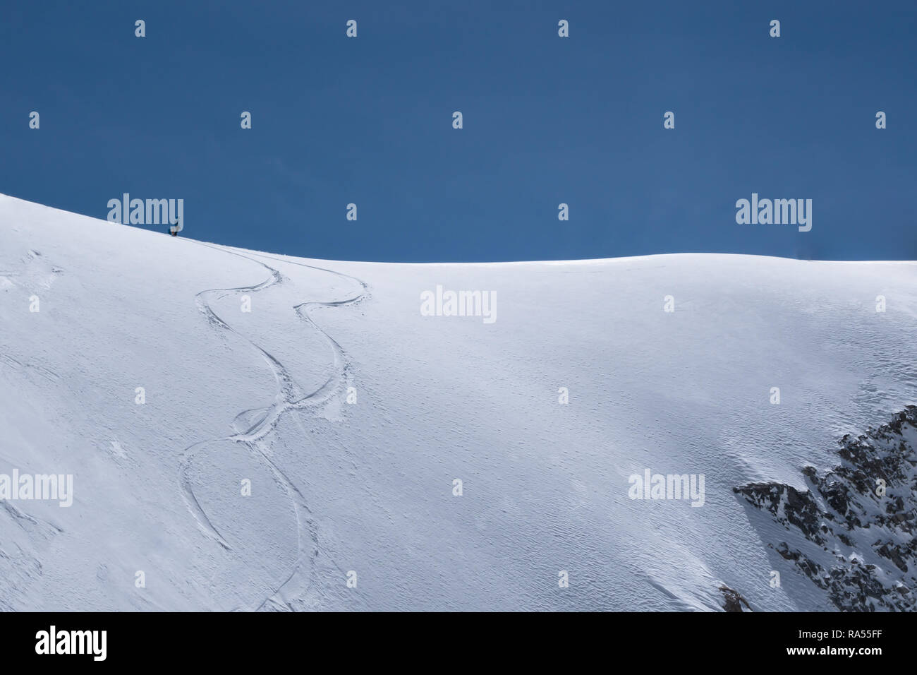 A single freeride skier on a snowy ridge is waiting to drop into  into the Col d'Argentiere, France approach and make his own tracks - Stock Image