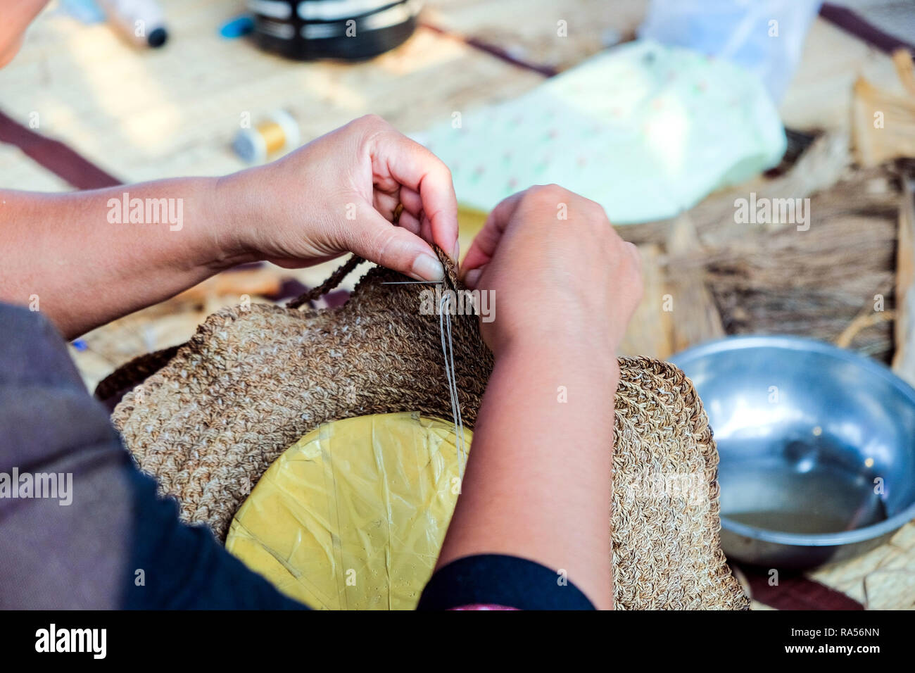 Hands of Thai female artisans is using a needle weaving sew hat that woven comes from plants. - Stock Image