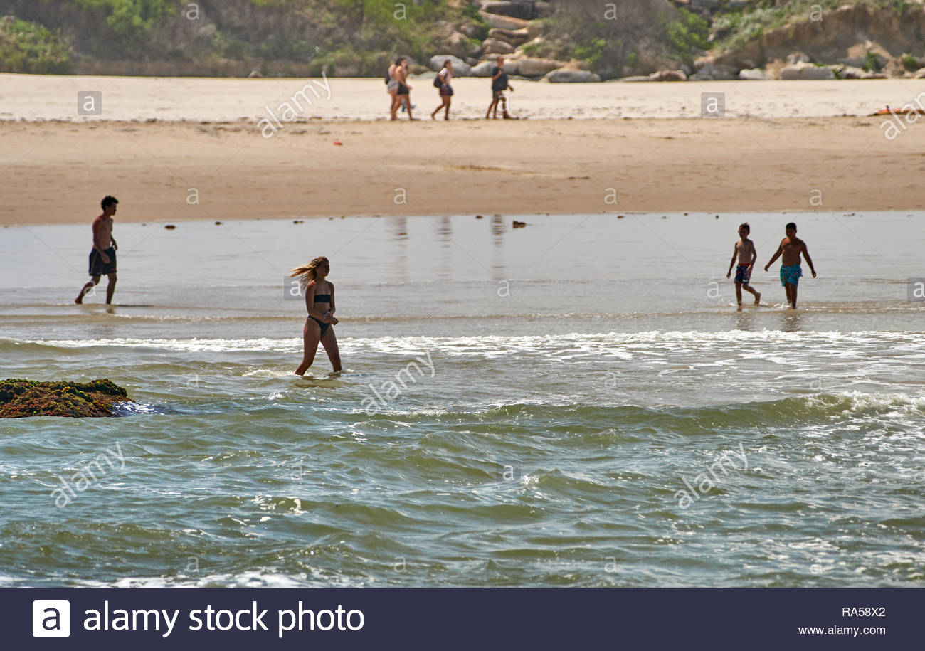 People of all ages - children, teenagers and adults - enjoying the sand and salt water, on a hot summer's day at Turners Beach, Yamba, NSW, Australia. - Stock Image