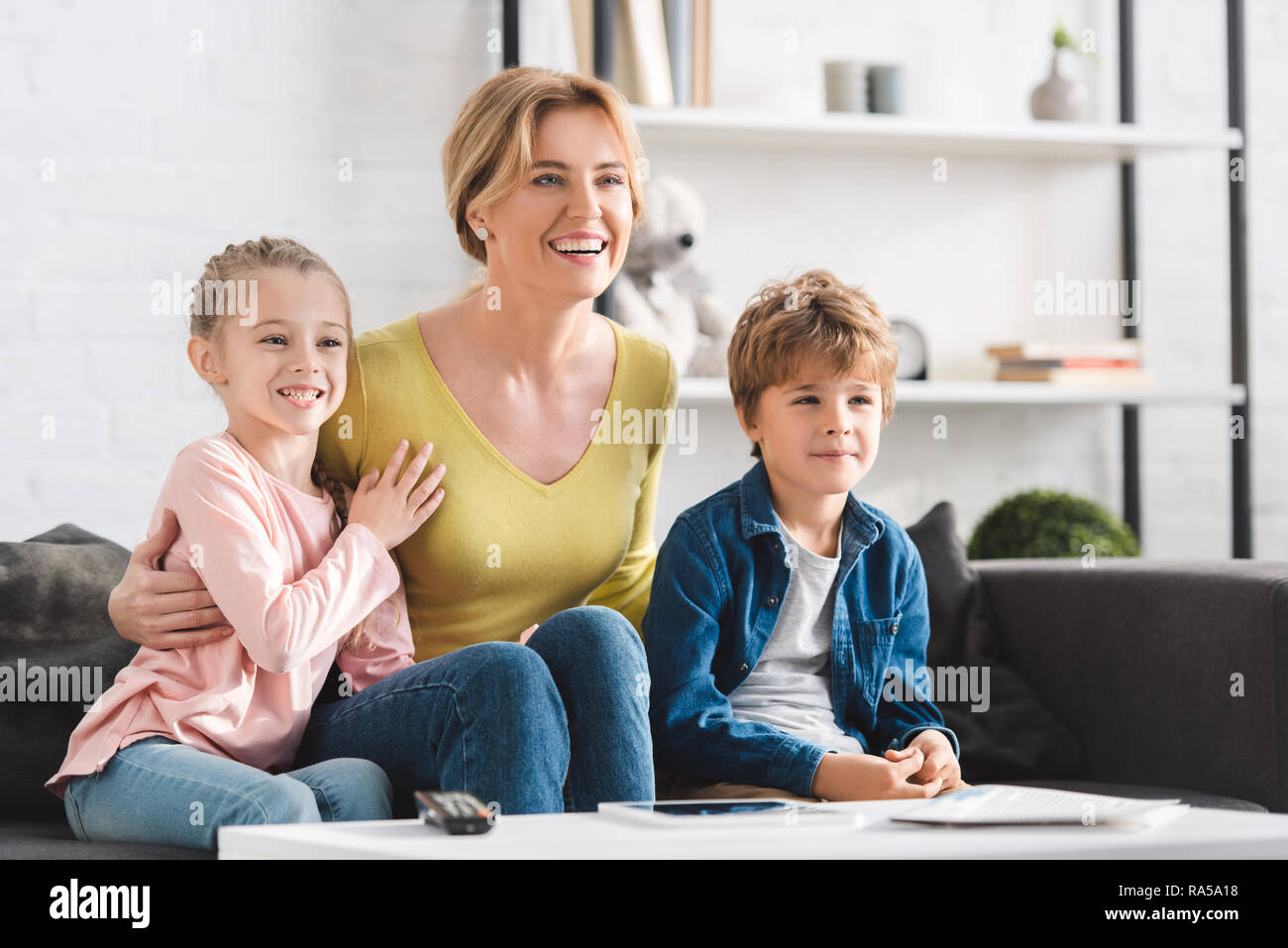 cheerful mother and beautiful smiling kids sitting in sofa
