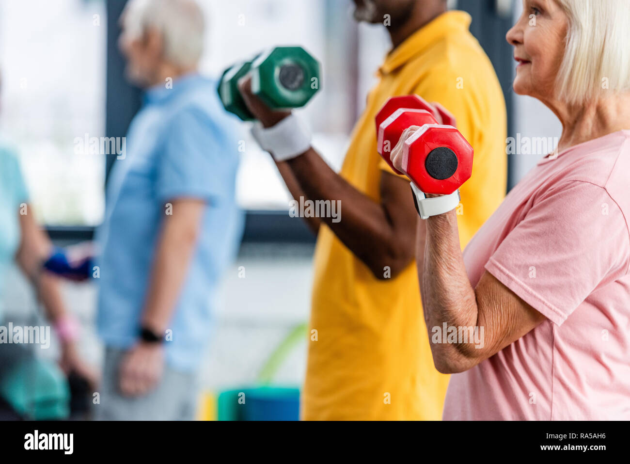 partial view of interracial mature couple doing exercise with dumbbells at gym Stock Photo