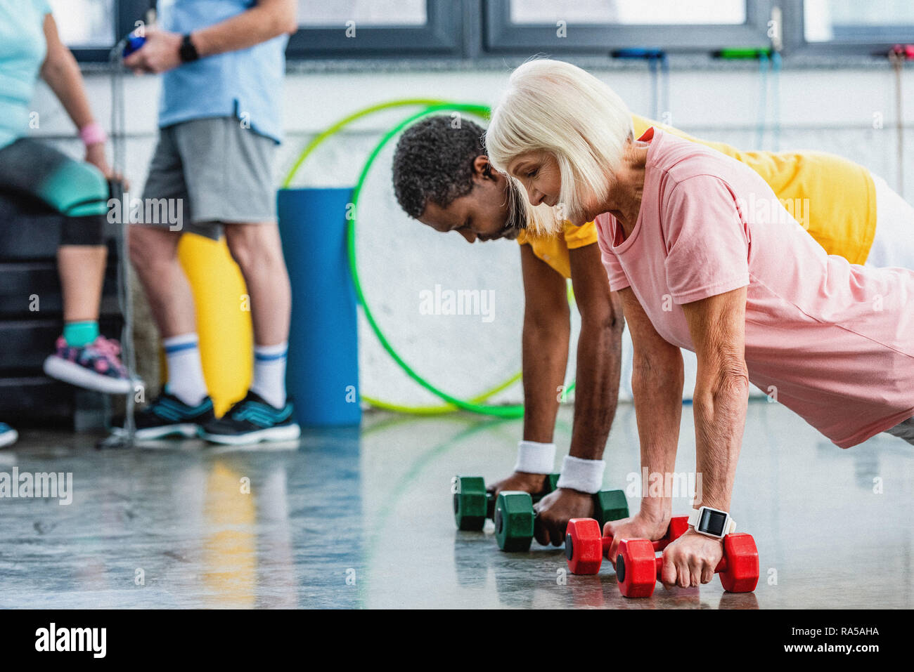 selective focus of interracial couple doing plank with dumbbells at gym Stock Photo