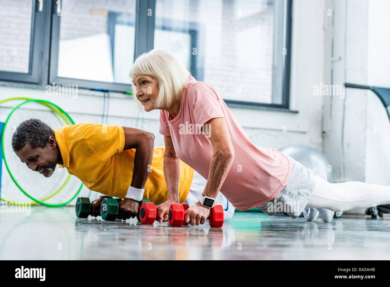 interracial mature couple doing push ups with dumbbells at gym Stock Photo