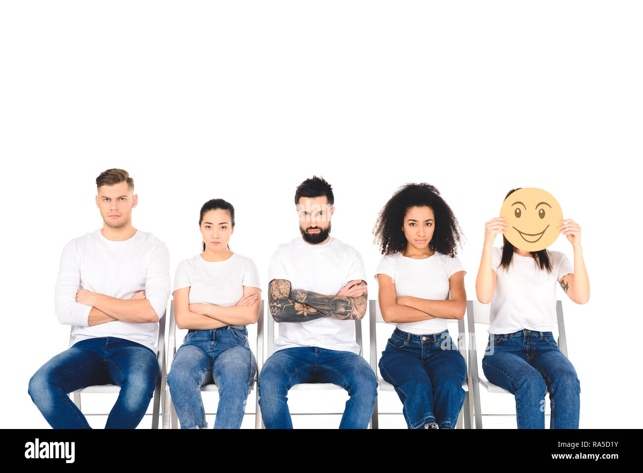 upset multicultural friends sitting on chairs with crossed arms while girl holding tricky sign isolated on white - Stock Image