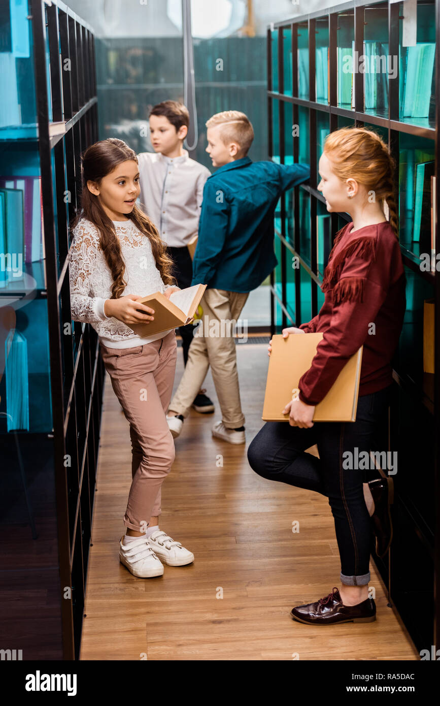 schoolchildren holding books and talking in library - Stock Image