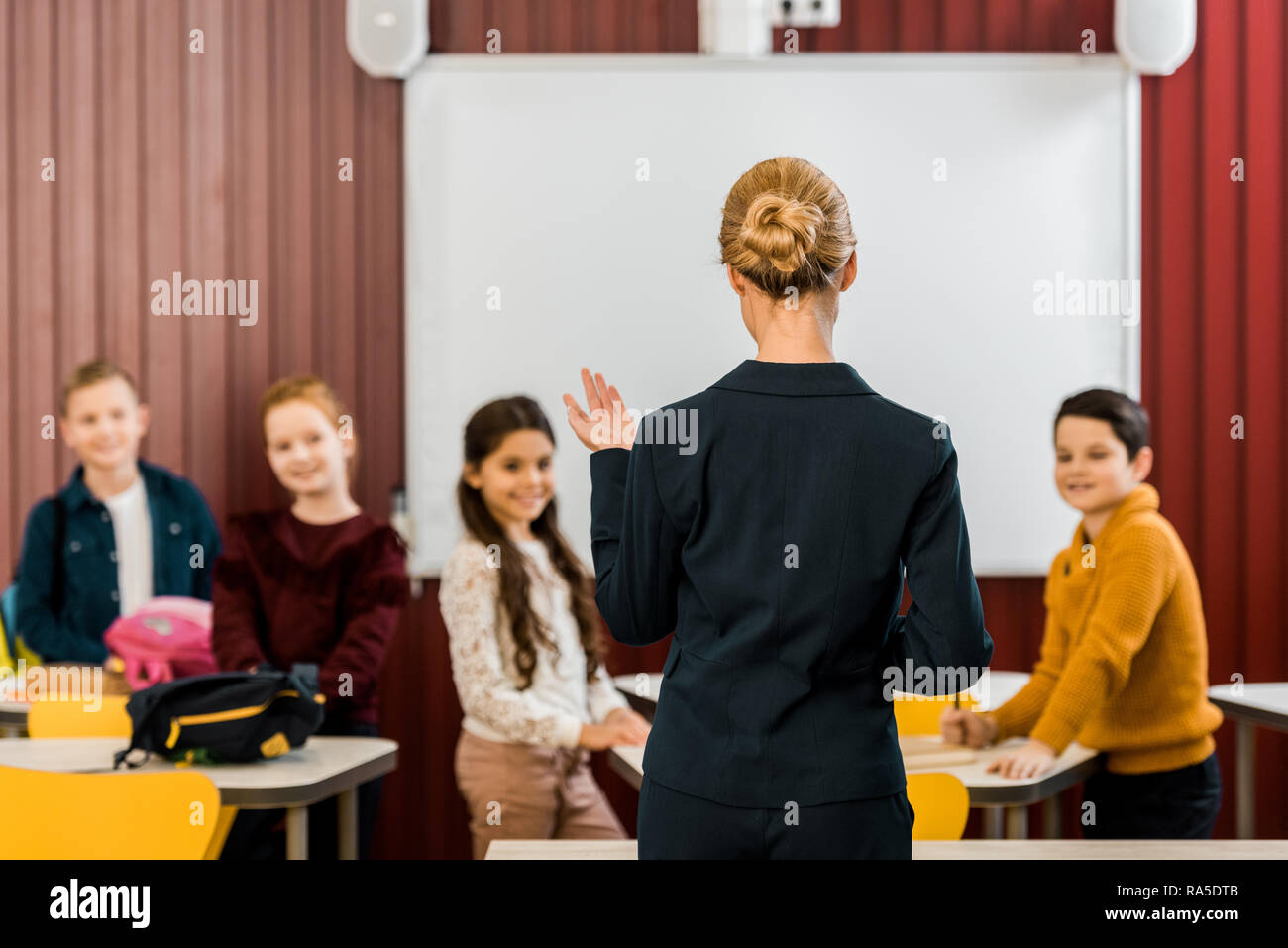 back view of teacher talking with smiling schoolchildren - Stock Image