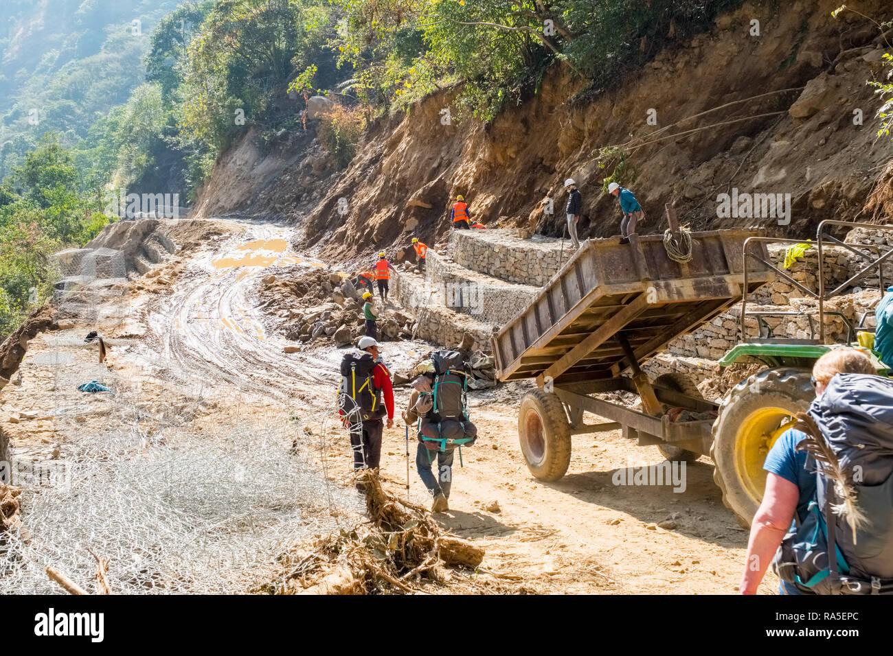 Trekkers walking through road construction work on the Annapurna Circuit trek, Nepal - Stock Image