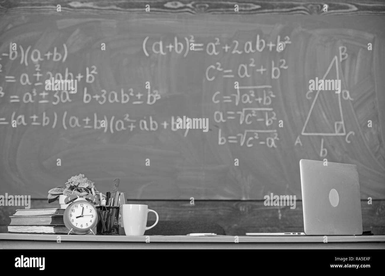 Teachers attributes. Table with school supplies alarm clock books and mug classroom chalkboard background. Working conditions which prospective teachers must consider. Traditional teachers workplace. - Stock Image