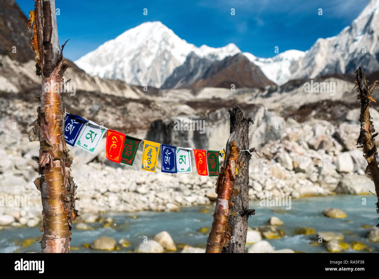 Prayer flags with glacial river and snow capped mountains in distance, typical Himalayan scenery on the Annapurna Circuit trek, Nepal - Stock Image