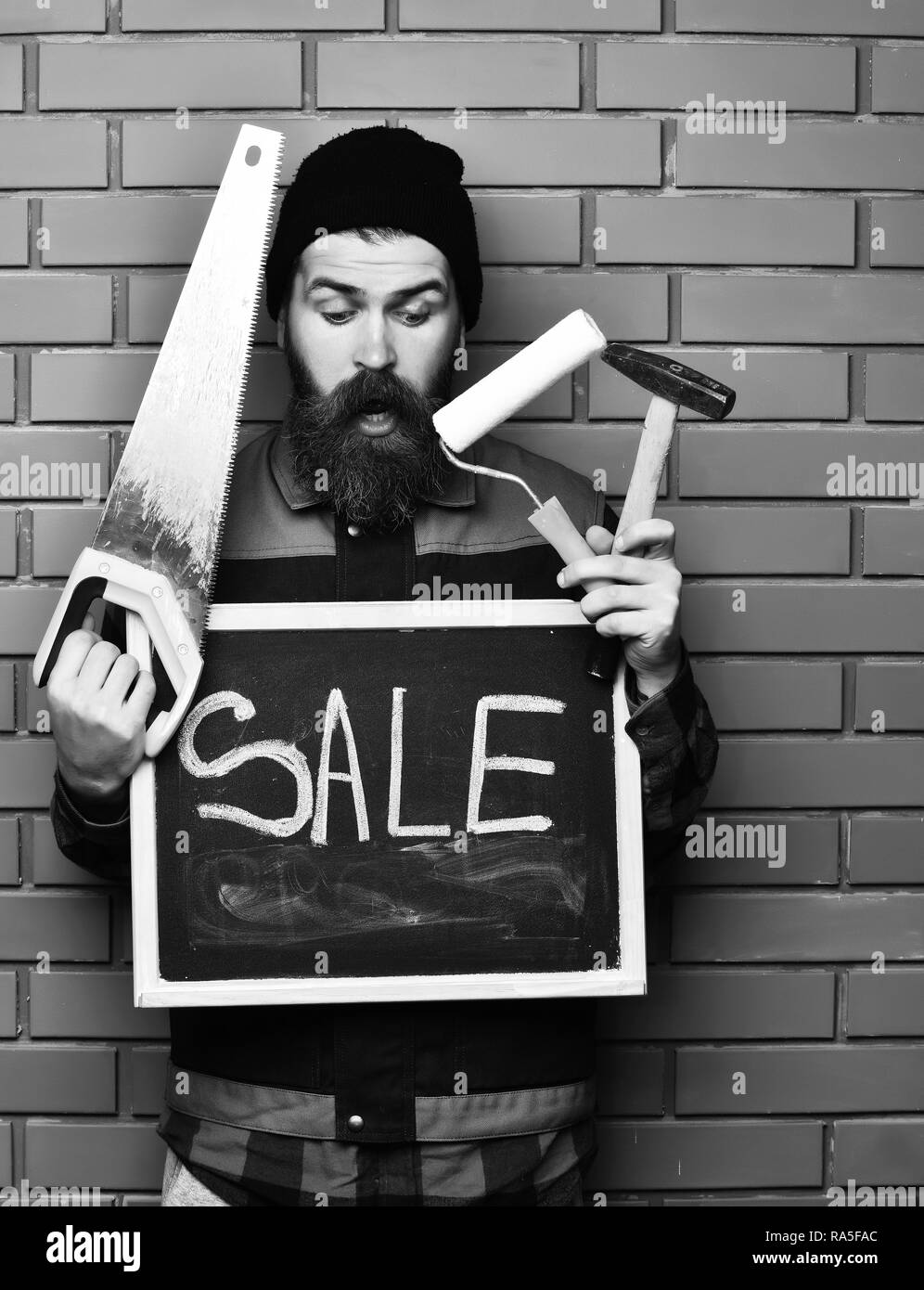 bearded foreman, long beard, brutal caucasian hipster with moustache holding various building tools: saw, hammer, roller paint, board with inscription sale with surprised face on brick wall background - Stock Image