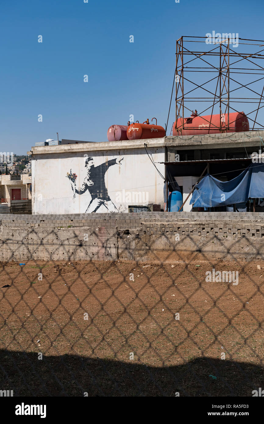 A mural by the elusive British street artist Banksy covers a wall in the West Bank village of Beit Sahour. Palestine Stock Photo