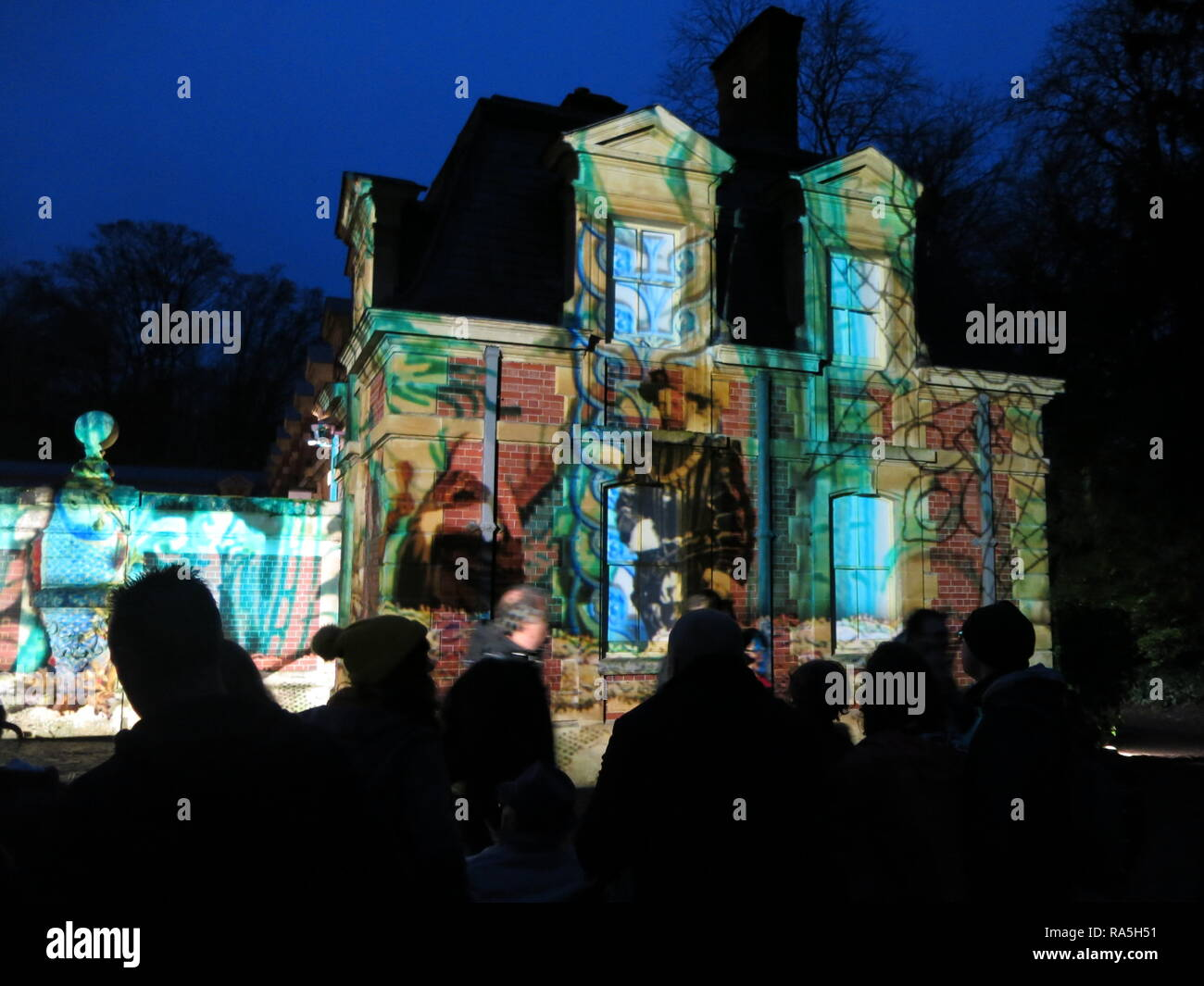 Audience silhouetted in the dark, watching the festive illuminations projected onto the walls of the stable block at Waddesdon Manor, Christmas 2018 - Stock Image