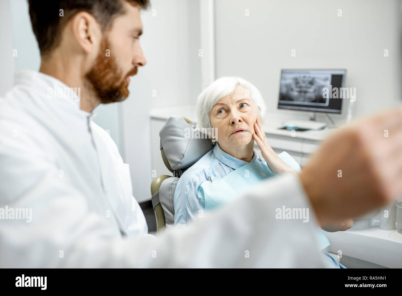 Worried elder woman during the consultation with handsome dentist showing panoramic x-ray in the dental office Stock Photo