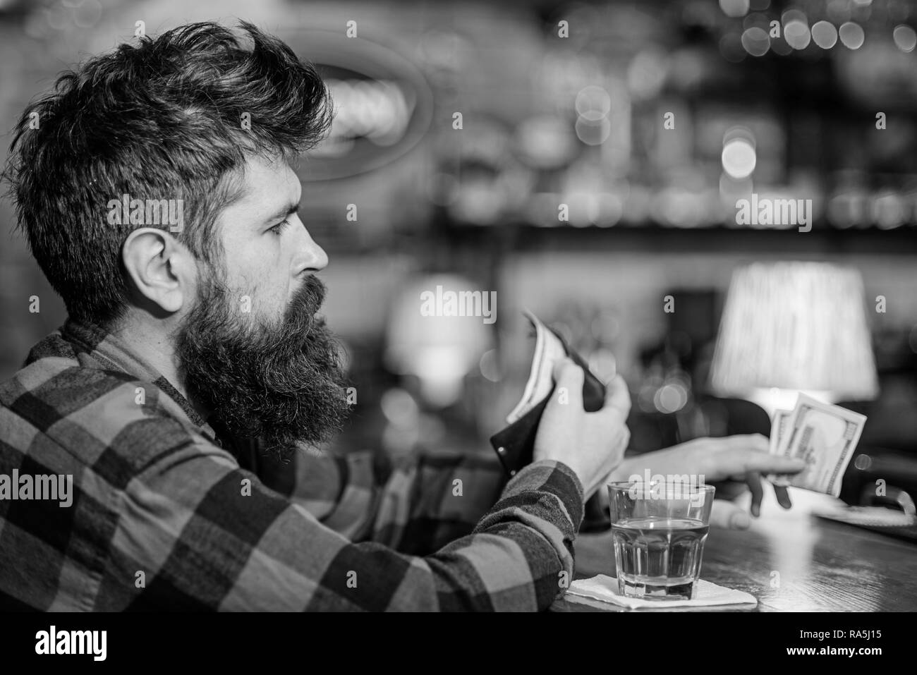Depression and alcoholism concept. Guy spend leisure in bar, defocused background. Man with busy face sit alone in bar or pub near bar counter. Hipster holds wallet, counting money to buy drinks. - Stock Image