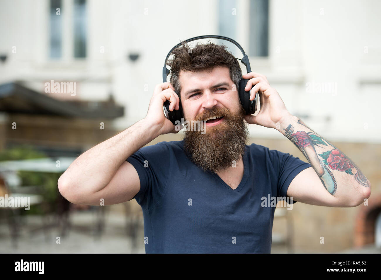 Man bearded hipster with headphones listening music. Hipster enjoy high quality sound of song in headphones. Get music subscription. Enjoy free songs everyday. Excellent music in his playlist. - Stock Image