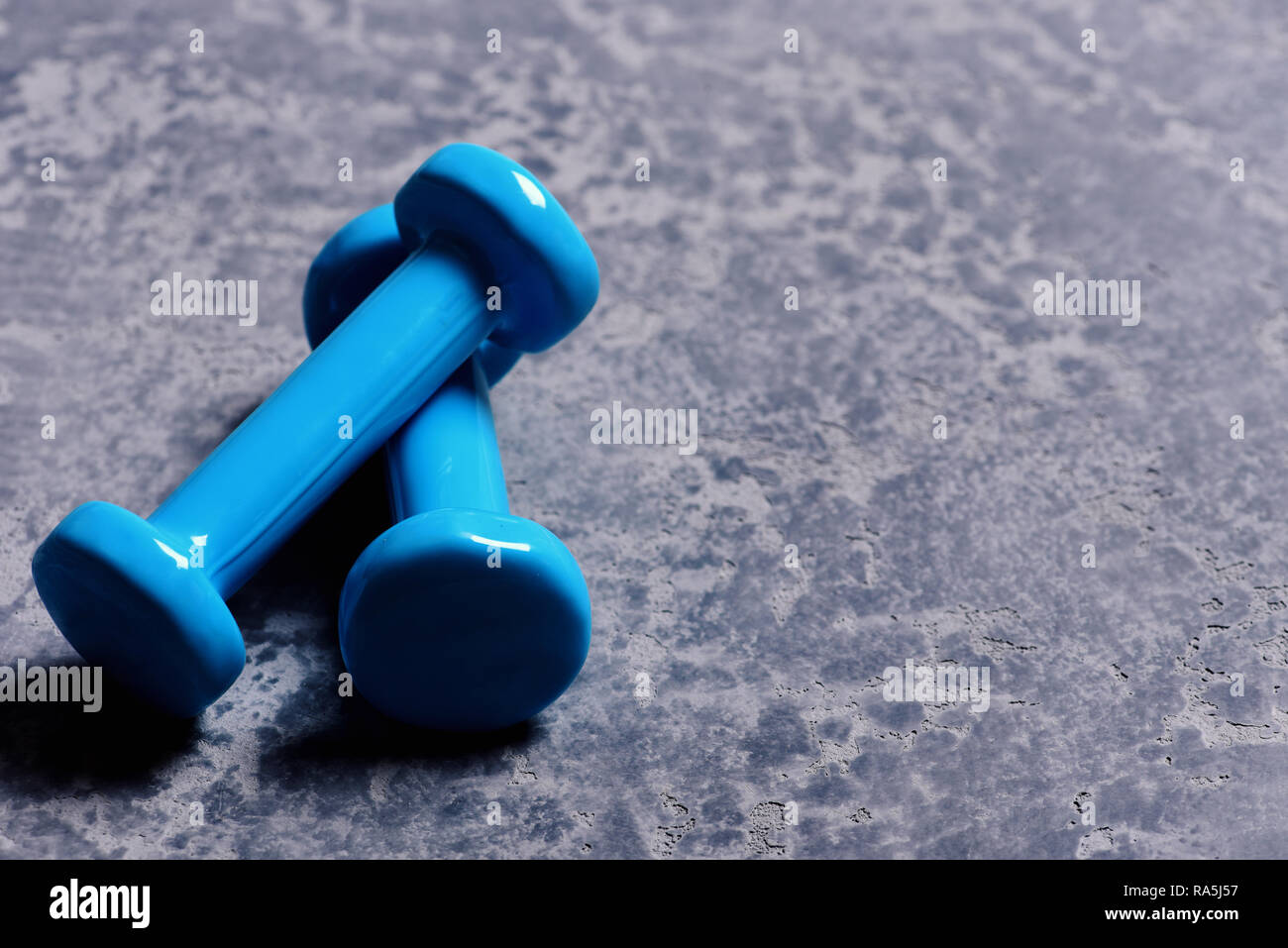 Barbells placed crosswise in close up. Dumbbells made of cyan plastic on defocused grey texture background. Sports and healthy lifestyle concept. Shaping and fitness equipment, copy space - Stock Image