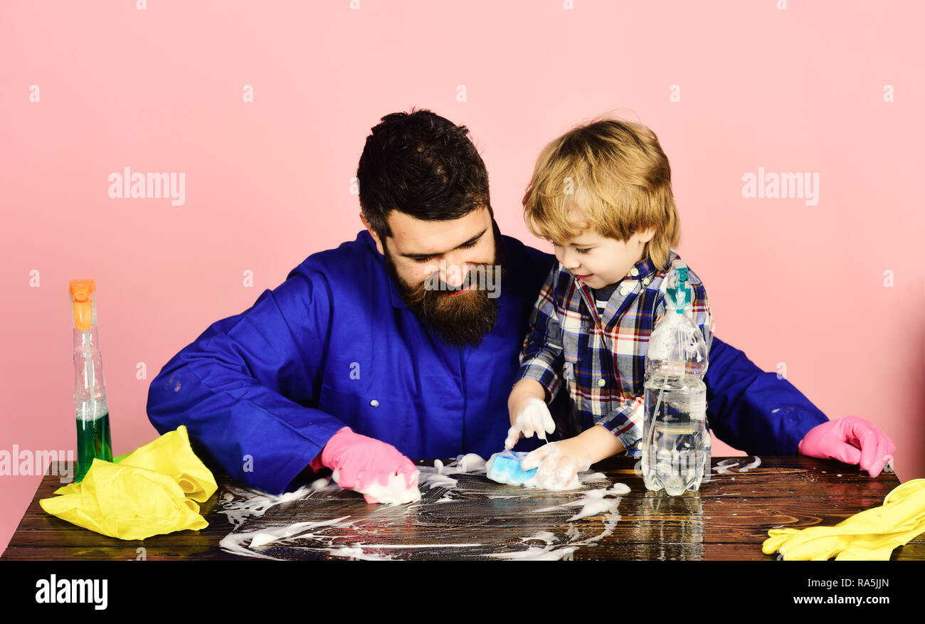 Man with cute child on pink background. Guy with beard and mustache in rubber gloves near cleaning props. Kid with father cleaning wooden table. Parents little helper concept. - Stock Image