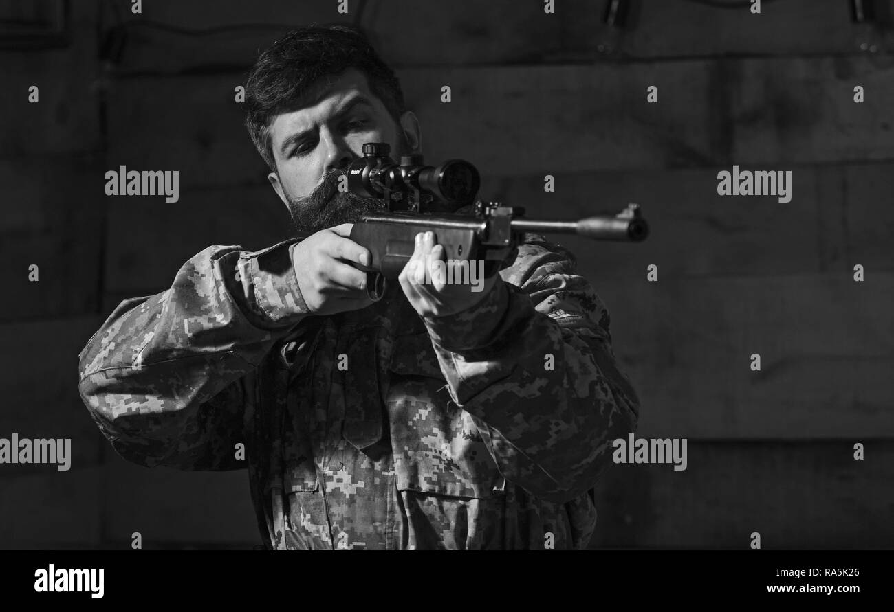 Man with beard wears camouflage clothing, wooden interior background. Macho on strict face at gamekeepers house. Huntsman concept. Hunter, brutal hipster with gun aiming before hunting, copy space. - Stock Image