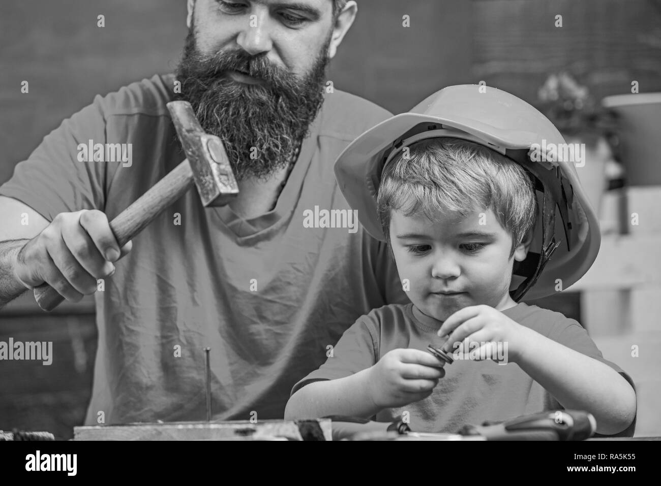 Masculine duties concept. Father, parent with beard teaching little son to use hobnails and hammer. Boy, child busy in protective helmet learning to hammering hobnails with dad. - Stock Image