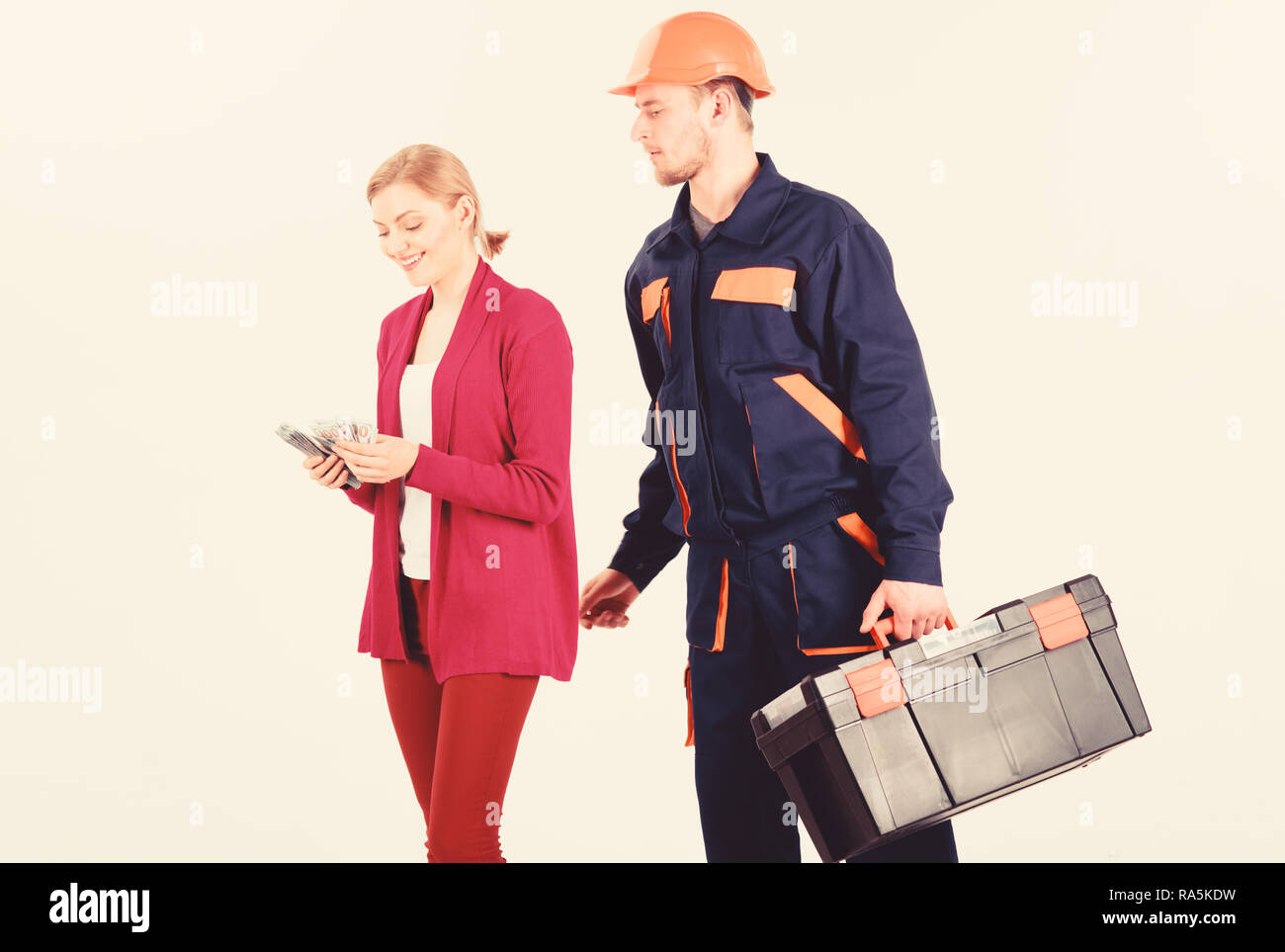 Builder in helmet looks at woman counting money, isolated on white background. Customer deceives repairman, builder, mechanic with toolbox. Repairer, builder wants salary for work. Payment concept. - Stock Image