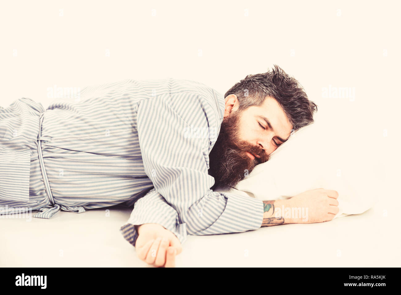 Man with relaxed face lies on pillow. Hipster with beard fall asleep. Fast asleep concept. Man with beard and mustache in deep sleep, white background. Hipster drowsy, wants to sleep, copy space. - Stock Image