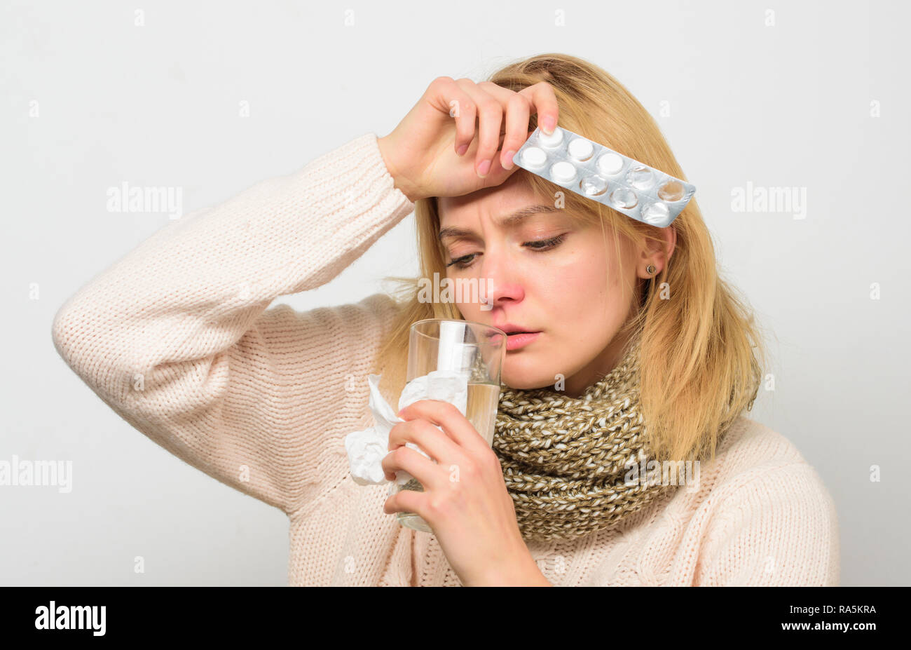 Headache and fever remedies. Woman tousled hair scarf hold tablets blister. Guidelines for treating fever. Take medications to reduce fever. Best fever reducer. Girl suffer headache and take medicine. - Stock Image