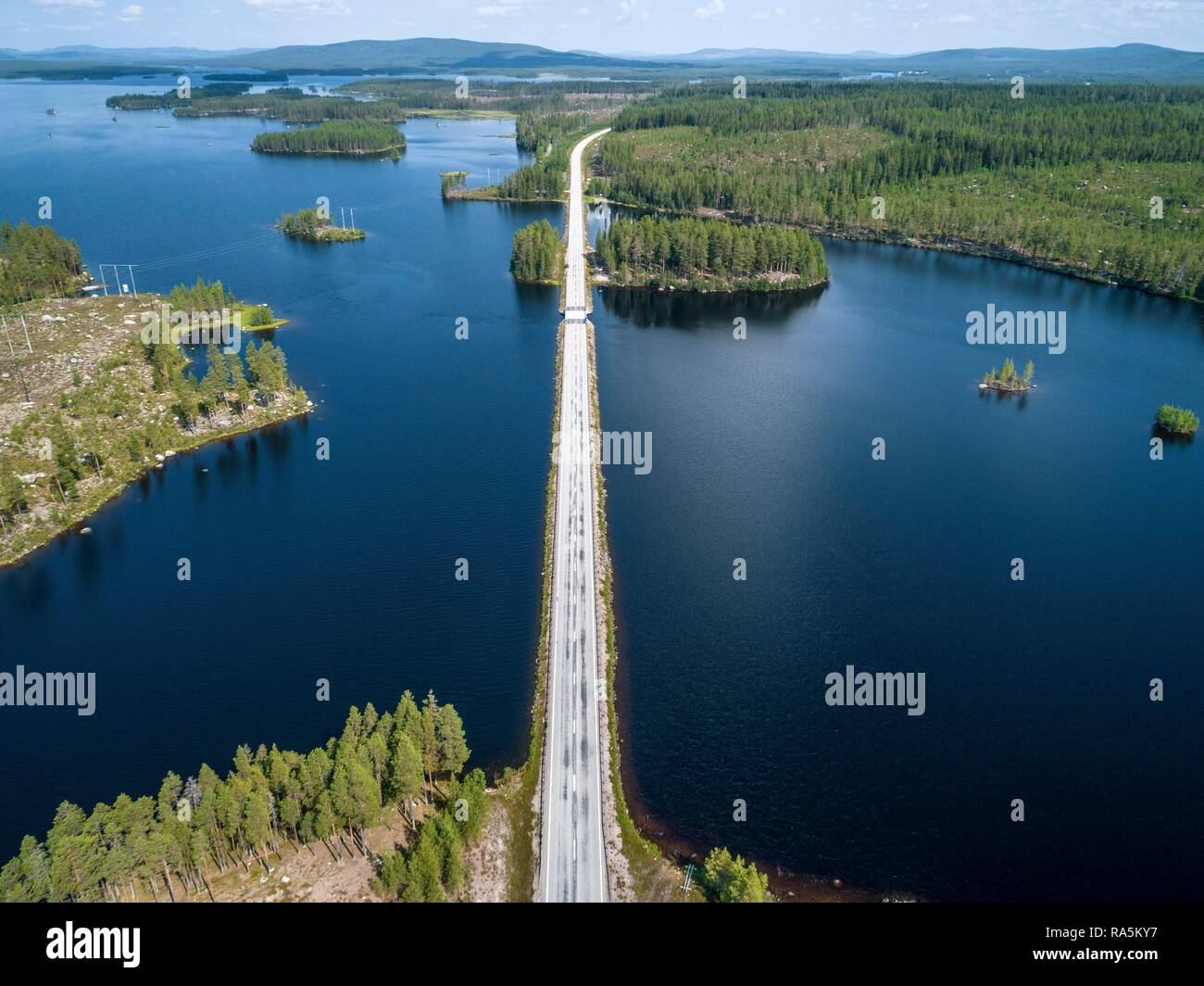 Drone shot, road runs across sea, boreal, arctic conifers, forest, Junsele, Västernorrlands län, Sweden - Stock Image