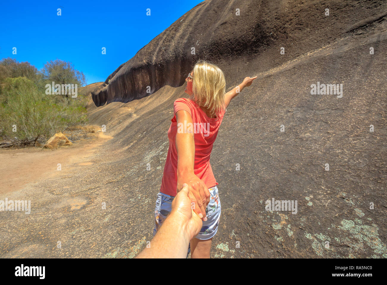 Follow me woman holding hands at side of wave rock along wave rock walk circuit in hyden western australia concept of the journey holding man by hand