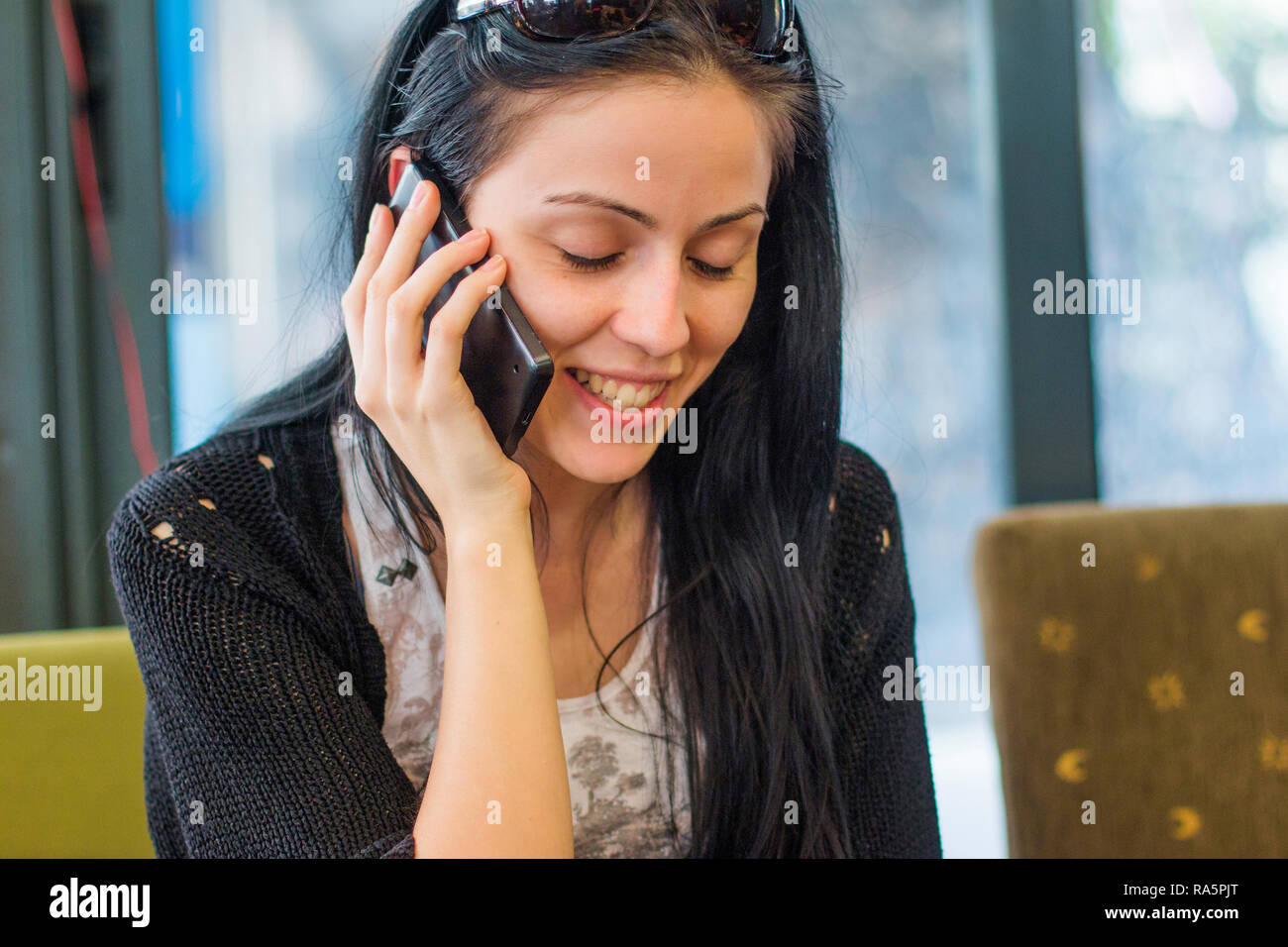 Happy young girl talking on mobile phone in cafe bar on the street Stock Photo