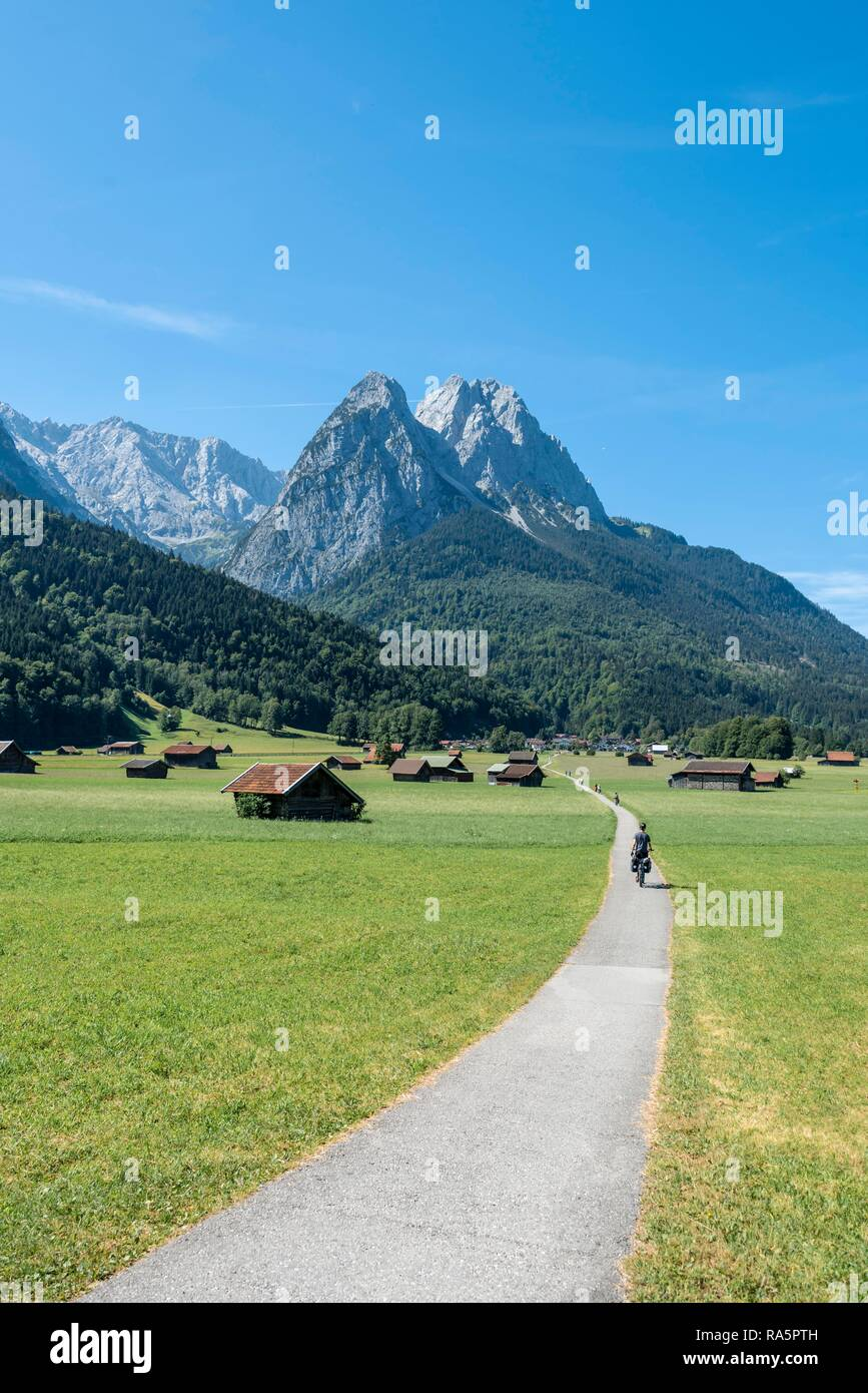 Cyclists on bike tour, cycle path with mountain bike, behind Zugspitze, Tegernauweg, near Grainau, crossing the Alps - Stock Image