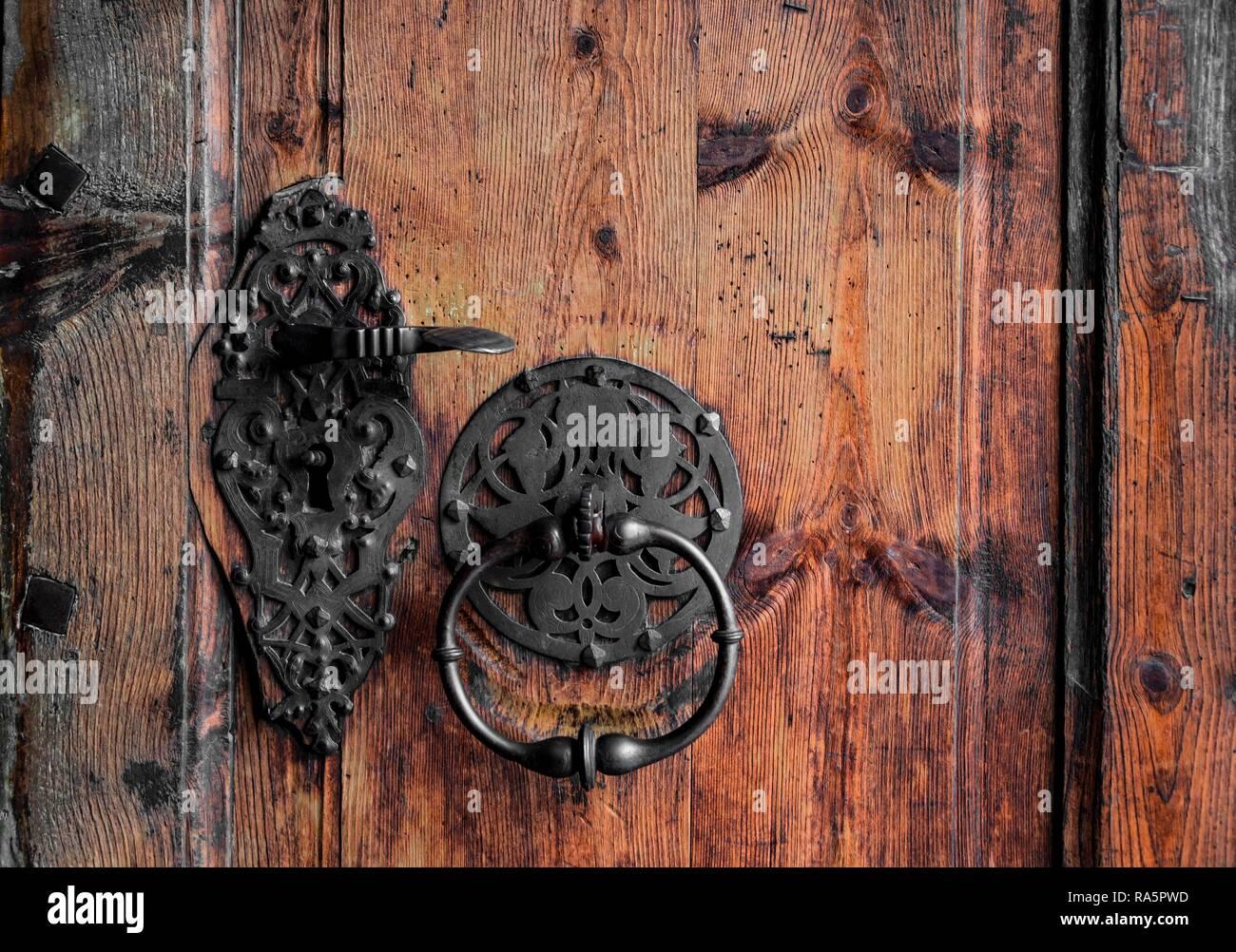 Forged door handle and knocker on an old wooden door, Austria - Stock Image